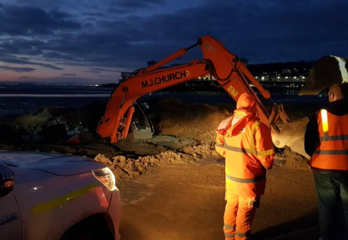 Police photos show the digger stuck fast as the tide came in