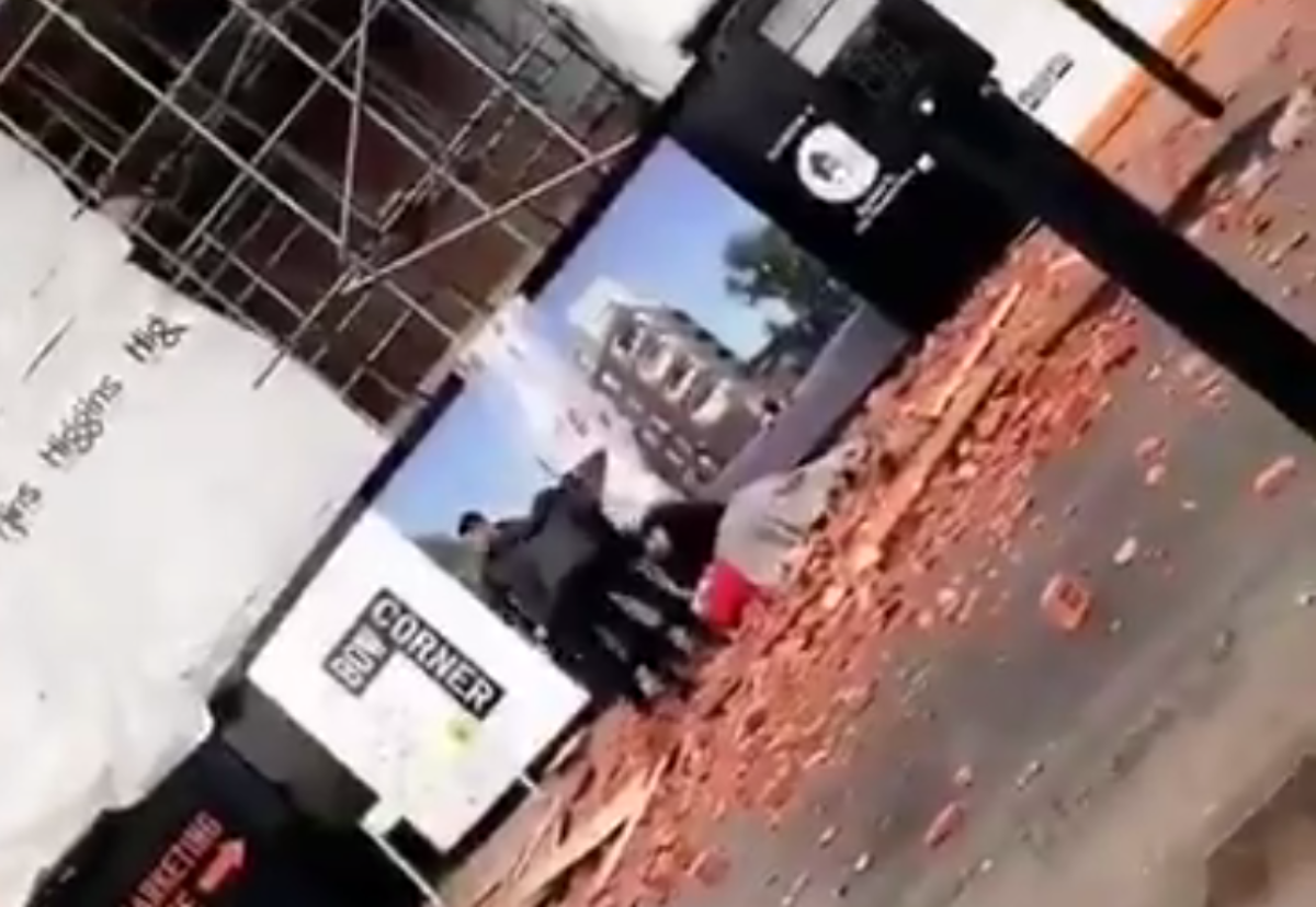 Shocked passers-by cover the prone woman hit by falling bricks
