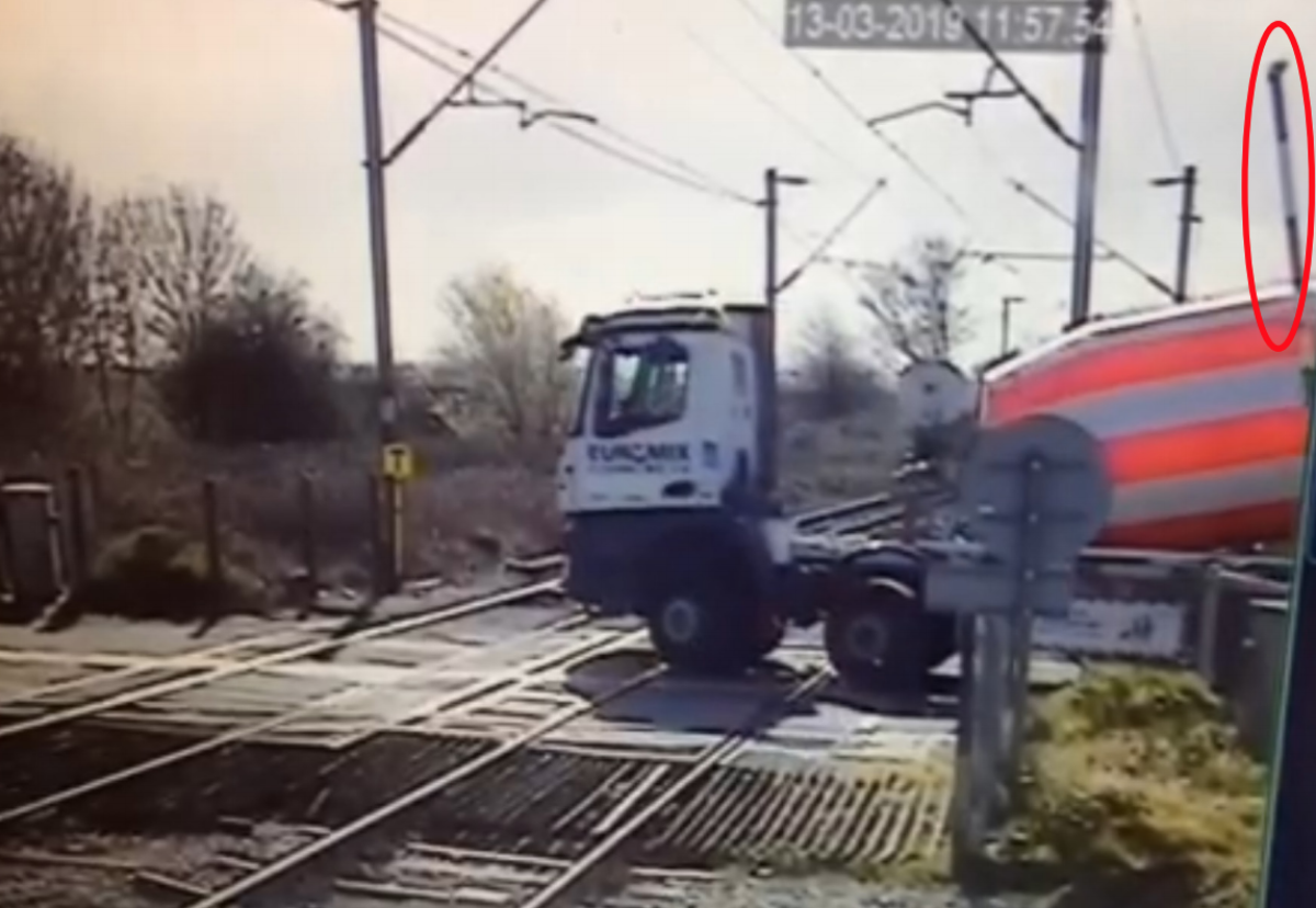Level crossing camera view showing lorry stopped and about to start reversing manoeuvre. The crossing barrier (highlighted) has started to lower